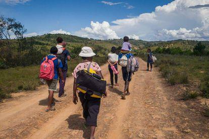 Varios residentes de Antananarivo caminan por la carretera nacional 7 que conduce al sur de Madagascar el pasado 27 de marzo de 2020. Han decidido abandonar la capital para regresar a su lugar de nacimiento por temor a la pandemia o porque han perdido sus empleos como resultado del cierre de la ciudad ordenado por las autoridades desde el 23 de marzo de 2020