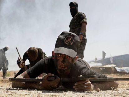 Un joven practica con un rifle de madera durante un entrenamiento militar de verano organizado por el grupo Yihad Islámica, en Gaza, Palestina.