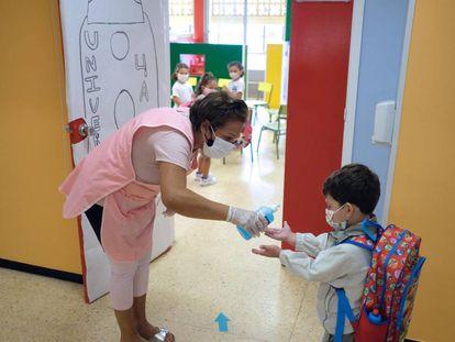 En la imagen, una profesora pone gel desinfectante en las manos a un niño en el colegio Millares Carló de Puerto del Rosario (Fuerteventura).