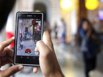 Un hombre intenta cazar un pokémon tras haberlo localizado, en una imagen de archivo.