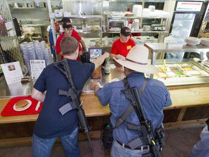 Dos hombres compran una hamburguesa después de un evento a favor de la posesión de armas en Houston.