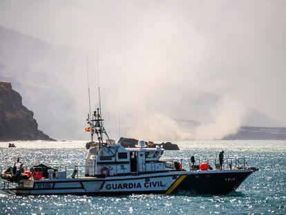 Una patrullera de la Guardia Civil frente a la columna de humo formada al llegar al mar la lava del volcán, este miércoles.