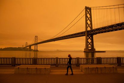 Una mujer camina por el embarcadero, en las cercanías del puente de la Bahía de San Francisco, bajo un cielo lleno de humo, por los incendios en California.