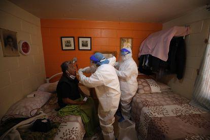 Dos médicos realizan una prueba de covid-19 a un paciente de 74 años, en su casa en el barrio de Venustiano Carranza de Ciudad de México.