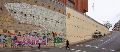 El tiburón del artista Blu, en el barrio del Carmel de Barcelona, tapado parcialmente por el Ayuntamiento para reparar el muro.