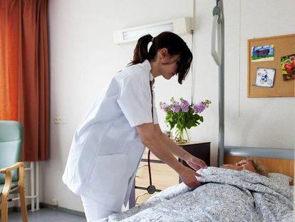 Una doctora, junto a una paciente en un centro sanitario.