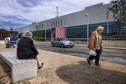 Usuarios del transporte público esperan la llegada del autobús en el hospital universitario Son Espases, en Palma.