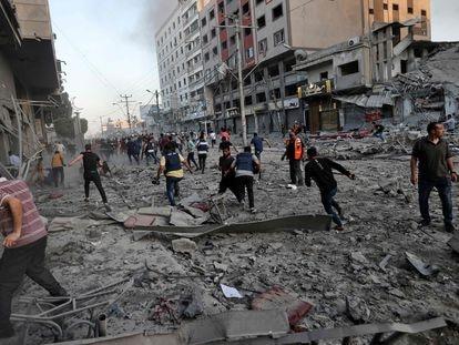 Personal de salvamento y vecinos palestinos corren entre los escombros frente de la Al-Sharouk, que se derrumbó tras un ataque aéreo de Israel, en la ciudad de Gaza.