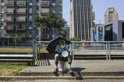 Un hombre pide limosna sentado en la avenida Libertador de Caracas. / ANDREA HERNÁNDEZ
