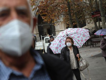 Gente paseando, protegida con mascarillas.