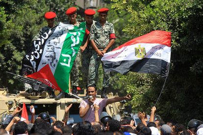 Policías observan a un grupo de manifestantes con las banderas de Egipto y Palestina durante una protesta en la embajada de Israel en El Cairo