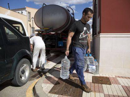 Un vecino de Fuente de Piedra (Málaga) recoge agua de un camión cisterna para abastecerse.