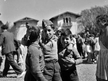 Tres niños delante de un palacio convertido en escuela, en 1937.