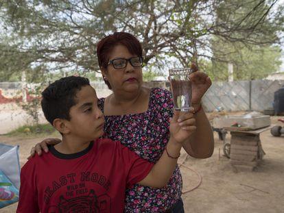 Marisol y su hijo, habitantes de Bacanuchi, observan un vaso de agua corriente, que no pueden beber desde el derrame de 2014.