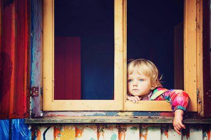 Un niño mira por la ventana.