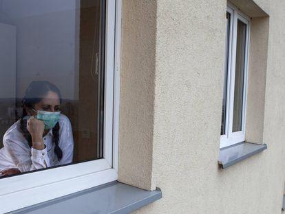 Una mujer mira a través de una ventana.