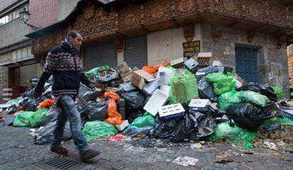 Un hombre pasa junto a la basura acumulada en una calle del centro de Granada.