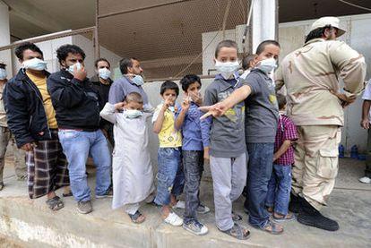 Varios niños aguardan con máscaras en la fila para ver el cadáver de Gadafi en Misrata.