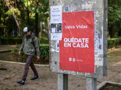 Un hombre camina junto a un cartel de la campaña 'Quédate en casa' del Gobierno de Ciudad de México.