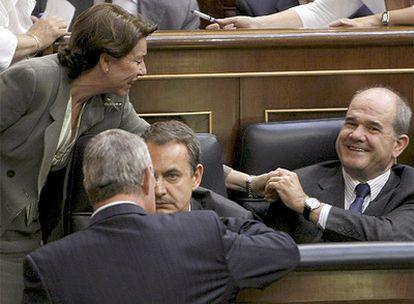 El presidente del Gobierno, José Luis Rodríguez Zapatero, habla con Jesús Caledera, de espaldas, durante las votaciones que se han llevado a cabo hoy en el Congreso