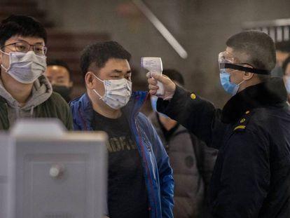 Controles para medir la temperatura en una estación de tren de Pekín. En vídeo, la OMS evita decretar la emergencia internacional por el virus de Wuhan.