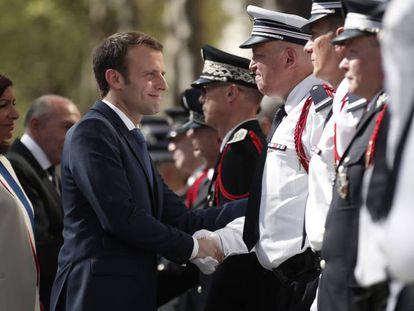 El presidente Macron, junto a la alcaldesa de París, Anne Hidalgo, saluda a policías en el homenaje a Xavier Jugele, agente muerto en un ataque el pasado año en los Campos Elíseos.