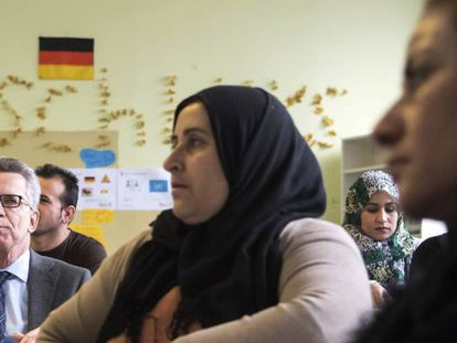 El ministro alemán del Interior, Thomas de Maiziere, visita a unos solicitantes de asilo.