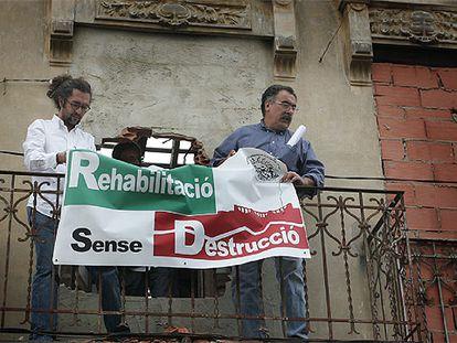 Faustino Villora (derecha) y otro miembro de Salvem El Cabanyal, ayer, colocan una pancarta en uno de los edificios pendiente de derribo.