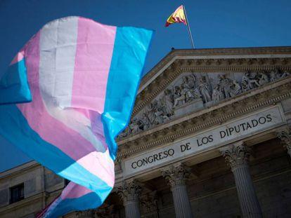 Una bandera trans ondea frente al Congreso de los Diputados.