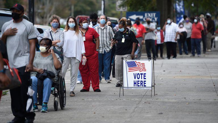 Decenas de personas esperan en fila para votar anticipadamente en las presidenciales, en Augusta, en octubre.