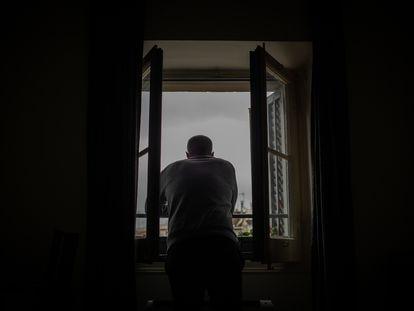 Una persona se asoma a su ventana en Barcelona en la segunda semana del estado de alarma