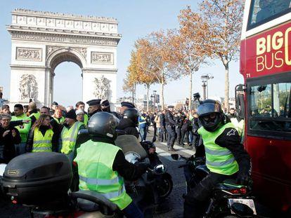 Manifestantes contra la subida de los combustibles bloquean el paso de un autobús turístico, este sábado en París.
