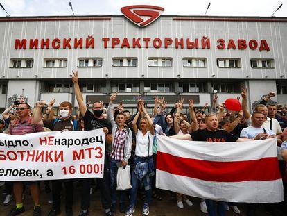 """Trabajadores de la empresa estatal de tractores MTZ durante la huelga de este viernes en la planta de Minsk. En la pancarta, su respuesta a Lukashenko, que aseguró que eran pocos y les llamó ovejas: """"No somos ovejas, somos trabajadores de MTZ; no somos 20, somos 16.000""""."""