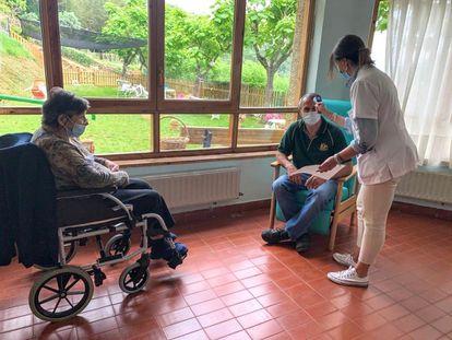 Una trabajadora de la residencia La Solana, de Aínsa (Huesca), toma la temperatura a un visitante, el día 9.