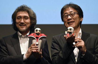 Dos ejecutivos de Toyota, responsables del proyecto de robótica, sujetan dos Kirobo Mini. El de la izquierda, con la funda para colocarlo en el posavasos del coche