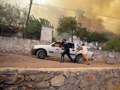 Varias personas escapan del avance de las llamas en el pueblo de Cokertme en la provincia turca de Mugla este lunes