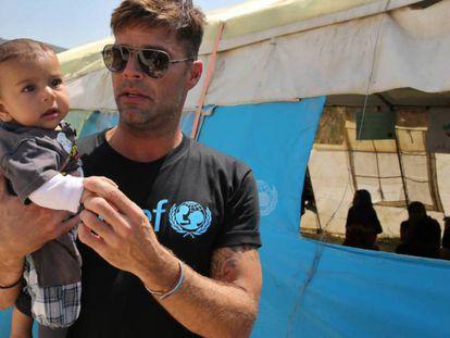 Ricky Martin junto a un bebé sirio en el campo de refugiados de Minnieh, cerca de Trípoli (Líbano).