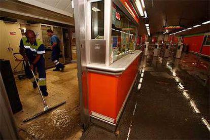 Un operario del metro limpia de agua la taquilla de la estación de Marqués de Vadillo.