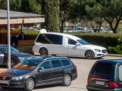 Empleados de la funeraria meten ayer un féretro en un coche en el Tanatorio Sur.