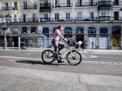 Un usuario de Bicimad pedalea por la Puerta del Sol de Madrid.