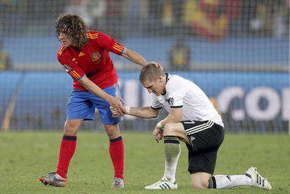 Puyol consuela a Schweinsteiger tras el partido.