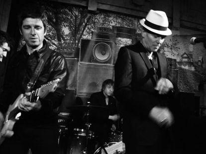 Noel Gallagher, a la izquierda con una guitarra, toca en el escenario con Paul Simonon, con sombrero, en su fiesta de cumpleaños en un bar del centro de Londres.