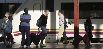 Varios pasajeros de tren en la estación de Chamartín (Madrid).