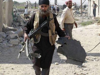 Un miembro del EI lleva un pedazo de un avión caído en Raqa (Siria).