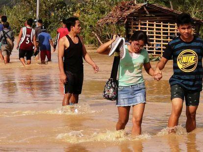 Un grupo de personas atraviesa una carretera inundada este jueves en Ormoc (Filipinas). En vídeo, imágenes del tifón Phanfone a su paso por el país del sudeste asiático.