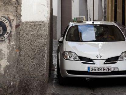 Un taxi avanza por la calle de San Juan de los Reyes, en el Albaicín.