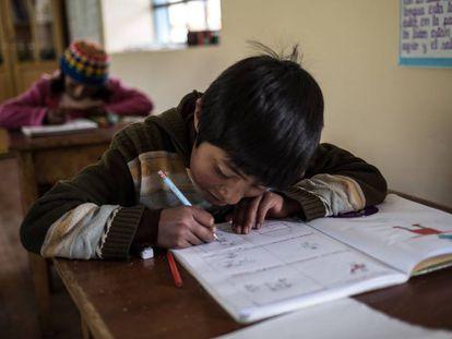 Un niño hace los deberes durante una clase en el colegio de Huaycho, una localidad campesina de Puno, en Perú.
