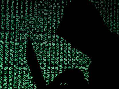 Un hombre encapuchado sostiene un portátil mientras se proyecta un código cibernético tras él.