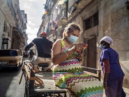 Una mujer mira su teléfono móvil mientras viaja en un carrito de bicicleta en La Habana, Cuba,