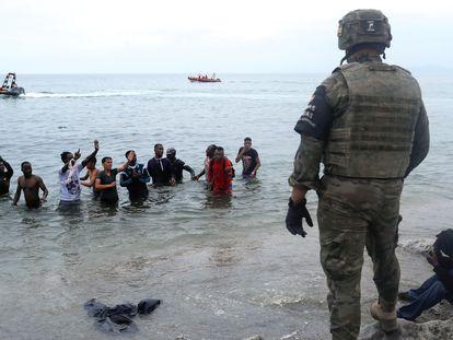 Un legionario contempla a jóvenes marroquíes en la playa de Ceuta tras haber cruzado a nado desde el vecino Marruecos.